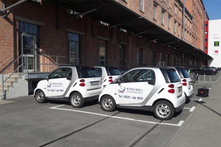Vier kleine Smarts mit Physiotherapie Kreisel Beklebung stehen vor der Roggenmühle Lehndorf